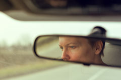 Αντανάκλαση του θηλυκού προσώπου στον οπισθοσκόπο καθρέφτη αυτοκινήτων Στοκ Εικόνες