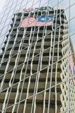 Αντανάκλαση του κτηρίου τραπεζών της HSBC με τη μαλαισιανή σημαία στα σύγχρονα παράθυρα γυαλιού οικοδόμησης στη Κουάλα Λουμπούρ,  Στοκ Εικόνες