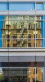 Αντανάκλαση του παλαιού κτηρίου τούβλου πολυόροφων κτιρίων στο νέο σύγχρονο υψηλός-Ri Στοκ Εικόνα