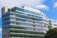 Αντανάκλαση των γερανών οικοδόμησης στα παράθυρα του σύγχρονου κτηρίου Στοκ Φωτογραφίες