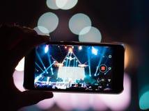 Αντανάκλαση των ελαφριών αποτελεσμάτων στο κινητό τηλέφωνο σε μια συναυλία (Gadge στοκ εικόνα