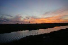 Αντανακλάσεις της σκιαγραφίας ηλιοβασιλέματος στο έλος κυπαρισσιών Στοκ Φωτογραφίες