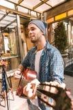 Αντανακλαστικός αρσενικός κιθαρίστας που πειραματίζεται με το παιχνίδι κιθάρων στοκ φωτογραφία