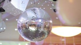 Αντανακλημένη σφαίρα disco σε μια άσπρη πυράκτωση των απεικονισμένων ακτίνων κλείστε επάνω φιλμ μικρού μήκους