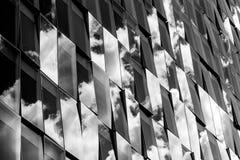 Αντανακλάσεις του νεφελώδους ουρανού σε μια πρόσοψη γυαλιού Στοκ Εικόνα