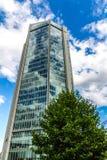 Αντανακλαστικά κτίρια γραφείων γυαλιού ενάντια στο μπλε ουρανό με τα σύννεφα και το φως ήλιων Στοκ φωτογραφία με δικαίωμα ελεύθερης χρήσης