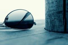 Αντανακλημένη λεπτομέρεια γυαλιών ηλίου στο ξύλινο υπόβαθρο Έννοια μόδας σε κυανό Στοκ εικόνα με δικαίωμα ελεύθερης χρήσης
