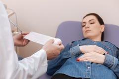 Ανταλαγμένος άριστος ειδικός που εξετάζει γυναικεία electrocardiographic tracings Στοκ Εικόνες