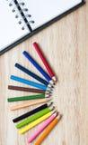 Αντικείμενα γραφείων και arte χαρτικών στον ξύλινο πίνακα με ένα σημειωματάριο Στοκ Εικόνα