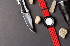 Αντικείμενα κυνηγιού, που διπλώνουν το μαχαίρι κυνηγιού, κόκκινο smartwatch και blac Στοκ φωτογραφία με δικαίωμα ελεύθερης χρήσης