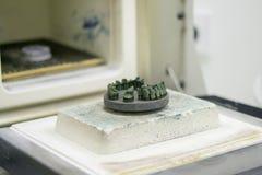 Αντικείμενο που τυπώνεται στον τρισδιάστατο εκτυπωτή μετάλλων κοντά στον κλίβανο για τη συμπύκνωση μετά από την κινηματογράφηση σ στοκ εικόνες