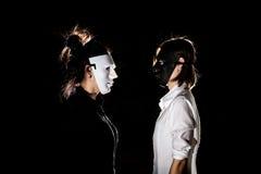 Αντιπαράθεση σύγκρουσης μεταξύ της όμορφης γυναίκας στη μαύρη μάσκα και Στοκ Φωτογραφία