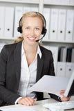 Αντιπρόσωπος εξυπηρέτησης πελατών που χρησιμοποιεί τα ακουστικά ενώ εκμετάλλευση Π Στοκ Εικόνες