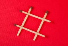 Αντιστοιχίες υπό μορφή hash στο κόκκινο υπόβαθρο Στοκ Εικόνες