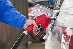 Αντλώντας βενζίνη ατόμων στο ασημένιο αυτοκίνητο με το κόκκινο ακροφύσιο καυσίμων Στοκ Φωτογραφία