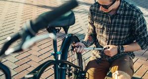 Αντλώντας ποδήλατο ροδών ποδηλατών νεαρών άνδρων, που προετοιμάζεται για το ταξίδι, έννοια μεταφορών συντήρησης Στοκ φωτογραφία με δικαίωμα ελεύθερης χρήσης