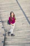 Ανυψωμένη άποψη ένα νέο ενήλικο κορίτσι που θέτει το ξύλινο ΛΦ περιστασιακών ενδυμάτων Στοκ Εικόνα