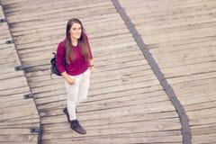Ανυψωμένη άποψη ένα νέο ενήλικο κορίτσι που θέτει το ξύλινο ΛΦ περιστασιακών ενδυμάτων Στοκ Εικόνες