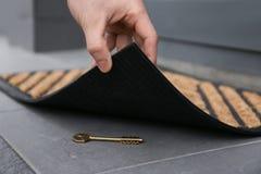 Ανυψωτικό χαλί πορτών ατόμων και εύρεση του κρυμμένου κλειδιού στοκ φωτογραφία με δικαίωμα ελεύθερης χρήσης