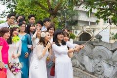 Ανόι, Βιετνάμ - 5 Απριλίου 2015: Ομάδα σπουδαστών στο βιετναμέζικο παραδοσιακό φόρεμα AO Dai που παίρνει τη φωτογραφία για τη μνή Στοκ φωτογραφία με δικαίωμα ελεύθερης χρήσης