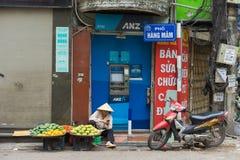 Ανόι, Βιετνάμ - 5 Απριλίου 2015: Φρούτα πωλήσεων προμηθευτών μπροστά από ANZ ATM Hang Mam στην οδό, Ανόι Στοκ Φωτογραφίες