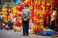 Ανόι, Βιετνάμ - 26 Ιανουαρίου 2017: Ο ηληκιωμένος παίρνει μια διακόσμηση και ένα λουλούδι αγοράς περιπάτων για το βιετναμέζικο σε Στοκ Εικόνες