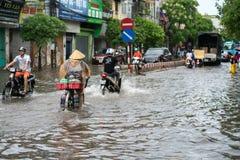 Ανόι, Βιετνάμ - 17 Ιουλίου 2017: Πλημμυρισμένη οδός Minh Khai μετά από τη δυνατή βροχή με ένα ποδήλατο ανακύκλωσης γυναικών που δ Στοκ φωτογραφίες με δικαίωμα ελεύθερης χρήσης