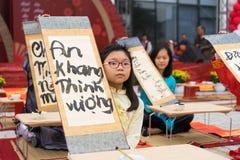 Ανόι, Βιετνάμ - 7 Φεβρουαρίου 2015: Παιδιά σχολείου στο παραδοσιακό φόρεμα AO Dai που μαθαίνουν με την καλλιγραφία στο βιετναμέζι Στοκ Φωτογραφία