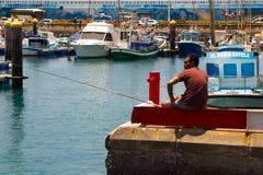 Ανύπαντρο που αλιεύει από το συγκεκριμένο λιμενοβραχίονα στη συσσωρευμένη μαρίνα στο Los Cristianos στο νησί Teneriffe Στοκ εικόνα με δικαίωμα ελεύθερης χρήσης