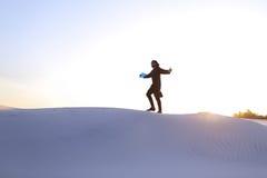 Ανύψωση αρσενικού μουσουλμάνου στην κορυφή του αμμόλοφου άμμου πέρα από την άσπρη άμμο μέσα Στοκ Εικόνα