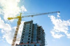Ανύψωση της λειτουργώντας οικοδόμησης κτηρίου γερανών στο φωτεινό μπλε ουρανό και του μεγάλου σύννεφου με το υπόβαθρο φλογών ήλιω Στοκ εικόνες με δικαίωμα ελεύθερης χρήσης