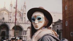 Ανώνυμη γυναίκα με τη μακρυμάλλη εξέταση πίσω τη κάμερα που φορά τη μάσκα καρναβαλιού στο τετράγωνο πόλεων της Βενετίας SAN Marco απόθεμα βίντεο