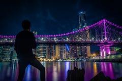 Ανώνυμο άτομο που εξετάζει τη γέφυρα και τη μητρόπολη τη νύχτα στοκ εικόνες με δικαίωμα ελεύθερης χρήσης