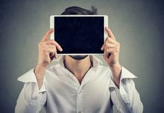 Ανώνυμο άτομο που καλύπτει το πρόσωπο με τον υπολογιστή ταμπλετών στοκ φωτογραφία με δικαίωμα ελεύθερης χρήσης