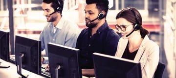 Ανώτατα στελέχη επιχείρησης με τις κάσκες που χρησιμοποιούν τους υπολογιστές στο γραφείο στην αρχή στοκ φωτογραφία με δικαίωμα ελεύθερης χρήσης