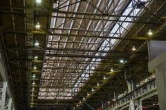 Ανώτατες πλάκες στα βιομηχανικά κτήρια, δομή χάλυβα στεγών με τους λαμπτήρες της σύγχρονης αποθήκης εμπορευμάτων ή εργοστάσιο Στοκ φωτογραφία με δικαίωμα ελεύθερης χρήσης