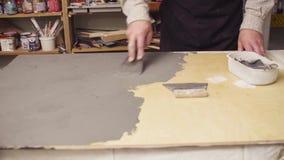 Ανώτερα ανθρώπινα χέρια που καλύπτουν μια ξύλινη επιφάνεια με το τσιμέντο απόθεμα βίντεο