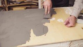 Ανώτερα ανθρώπινα χέρια που καλύπτουν μια ξύλινη επιφάνεια με το τσιμέντο φιλμ μικρού μήκους