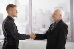 Ανώτερα και μέσος-ενήλικα χέρια τινάγματος επιχειρηματιών στοκ φωτογραφία