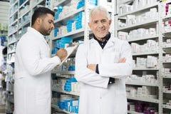 Ανώτερα μόνιμα όπλα φαρμακοποιών που διασχίζονται ενώ συνάδελφος που μετρά το ST Στοκ Εικόνες