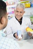 Ανώτερα προϊόντα εκμετάλλευσης φαρμακοποιών εξετάζοντας τον πελάτη στοκ εικόνες