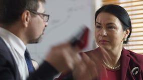 Ανώτερα ωρ. στελέχη κινηματογραφήσεων σε πρώτο πλάνο που συζητούν κατά τη διάρκεια του σπασίματος απόθεμα βίντεο