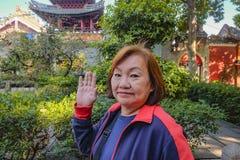 """Ανώτερες ασιατικές γυναίκες τουριστών που περπατούν ενώ πέστε """"γεια """"στη κάμερα στον προγονικό ναό στοκ εικόνες"""