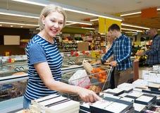 Ανώτερες καραμέλες αγοράς γυναικών σε μια υπεραγορά Στοκ Εικόνες
