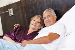 Ανώτερη αγκαλιά ζευγών στο κρεβάτι Στοκ Φωτογραφία