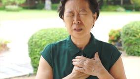 Ανώτερη ασιατική γυναίκα που έχει την επίθεση καρδιών, θωρακικός πόνος απόθεμα βίντεο