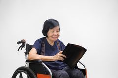 Ανώτερη ασιατική γυναίκα που χαμογελά διαβάζοντας το περιοδικό στοκ εικόνα