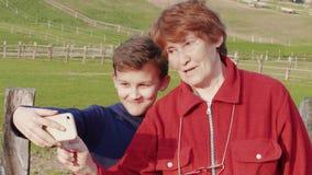Ανώτερη γυναίκα, αγόρι εφήβων που παίρνει selfie από το κινητό εξωτερικό φιλμ μικρού μήκους