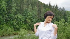 Ανώτερη γυναίκα με την κοντή σκοτεινή τρίχα που κάνει μια τεντώνοντας άσκηση για τη χαλάρωση το πρωί έξω πέρα από το τοπίο φιλμ μικρού μήκους