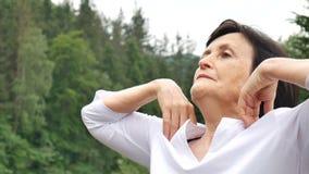 Ανώτερη γυναίκα με την κοντή σκοτεινή τρίχα που κάνει μια τεντώνοντας άσκηση για τη χαλάρωση το πρωί έξω πέρα από το τοπίο απόθεμα βίντεο